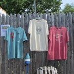 Blue, tan, red tees hang on this fence for sale.