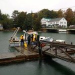 A boat on the water, dog with her full rain gear. Damariscotta