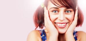 portrait of young girl with beautiful smile with hand on face against gradient pink background